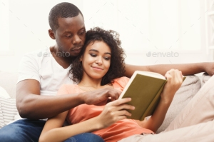 HAppy black couple reading together at home
